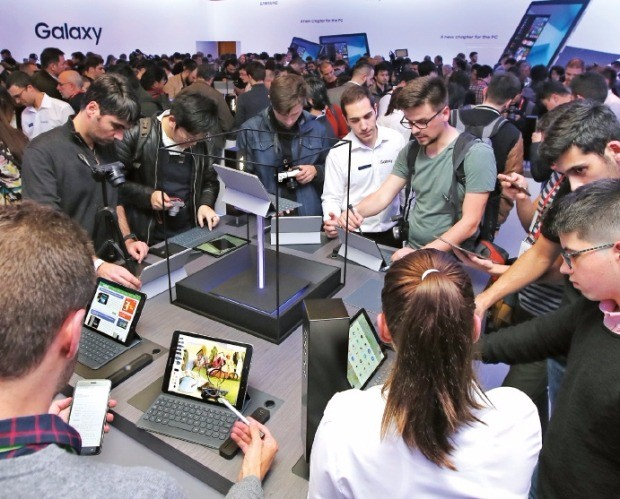 스페인 바르셀로나 카탈루냐 콩그레스센터에서 26일(현지시간) 열린 삼성전자 태블릿PC 발표 행사에서 참석자들이 '갤럭시탭S3'와 '갤럭시북'을 써보고 있다. 연합뉴스
