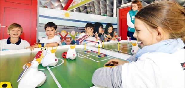 SK텔레콤이 27일(현지시간) 스페인 바르셀로나 유니버스 플라자에 설치한 '티움 모바일'에서 한국 봉동초등학교 어린이와 스페인 어린이들이 코딩교육용 로봇 알버트를 이용해 축구 게임을 하고 있다. SK텔레콤 제공