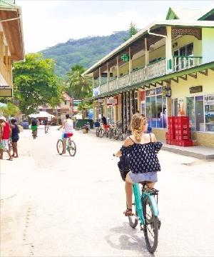 라디그 섬의 번화가를 자전거로 돌고 있는 여행객.