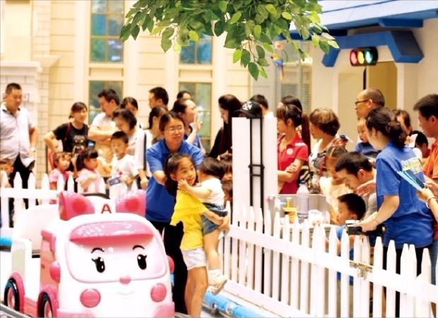 폴리파크 충칭점에서 아이와 부모들이 미니 캐릭터 자동차를 즐기고 있다.