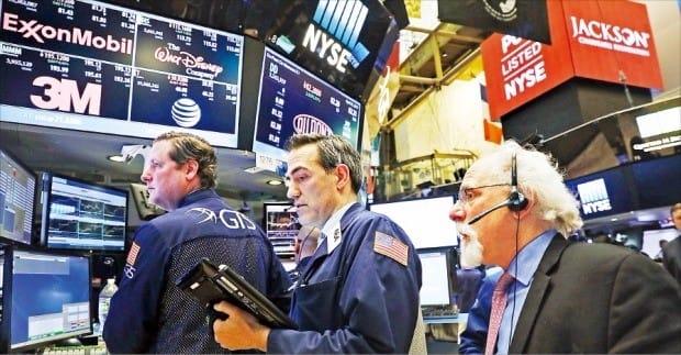 미국 나스닥지수가 6000선을 돌파하며 사상 최고치를 기록한 25일(현지시간) 뉴욕증권거래소(NYSE)의 주식 중개인들이 시세판을 들여다보고 있다. 뉴욕AFP연합뉴스