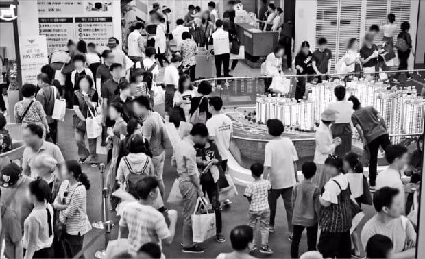 서울 강동구 '고덕 롯데캐슬 베네루체' 모델하우스를 찾은 예비청약자들이 지난달 28일 단지 모형도를 둘러보고 있다. 이 단지의 평균 청약경쟁률은 11.3 대 1을 기록했다. 한경DB