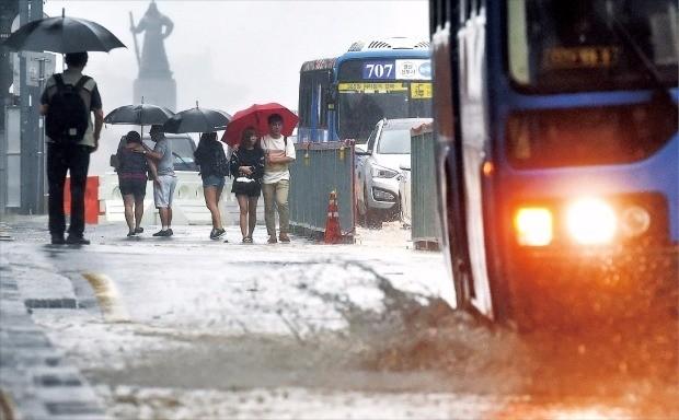 < 서울 133mm 폭우 > 서울, 인천 등 11곳에 호우경보가 내려진 23일 오후 버스 한 대가 보행로에까지 튈 정도로 큰 물보라를 일으키며 서울 세종대로를 지나고 있다. 이날 낮 12시까지 서울에만 133㎜에 달하는 비가 내렸다. 허문찬 기자 sweat@hankyung.com