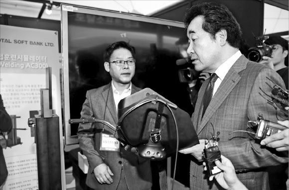이낙연 국무총리가 18일 서울 상암동 누리꿈스퀘어에서 열린 '코리아 VR 페스티벌 2017'에서 토탈소프트뱅크가 개발한 VR 용접 시뮬레이터에 대해 설명을 듣고 있다.  /연합뉴스