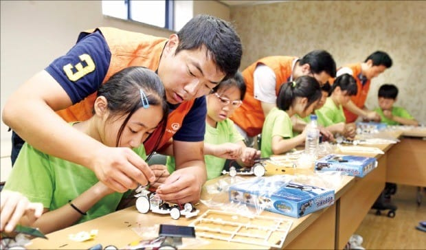 '내일을 위한 에너지 교실'에서 한화케미칼 직원들이 초등학생과 함께 태양광으로 움직이는 모형 자동차를 만들고 있다.  한화케미칼 제공
