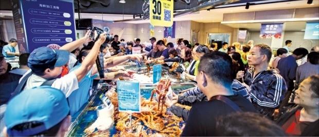 고객들이 지난 11일 중국 상하이 푸둥에 있는 알리바바의 신선식품 전문매장인 허마셴성 진차오점에서 수산물을 고르고 있다. 강동균 특파원