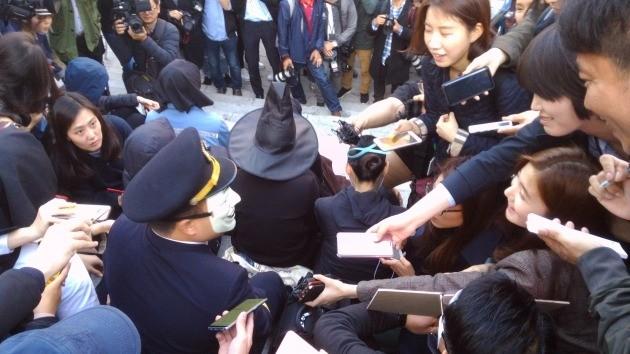 가면을 쓰고 등장한 한 대한항공 직원에게 취재진들이 몰리고 있다