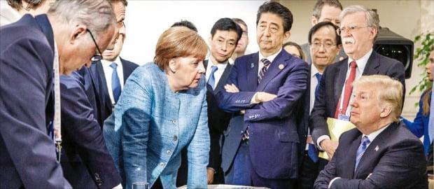 < 메르켈 '어필'에 팔짱 낀 트럼프 > 앙겔라 메르켈 독일 총리(가운데)가 9일(현지시간) 캐나다 퀘벡주 샤를부아에서 열린 주요 7개국(G7) 정상회의에서 탁자에 손을 짚은 채 팔짱을 끼고 앉아 있는 도널드 트럼프 미국 대통령(오른쪽)을 향해 무언가를 심각하게 얘기하고 있다.  /독일 연방정부 제공