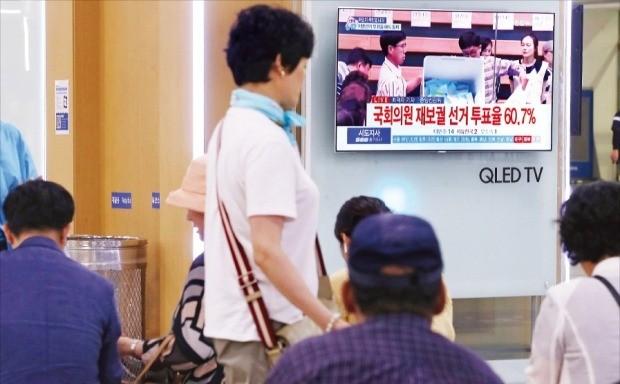 제7회 전국동시지방선거가 치러진 13일 시민들이 서울역에서 개표방송을 시청하고 있다. /연합뉴스