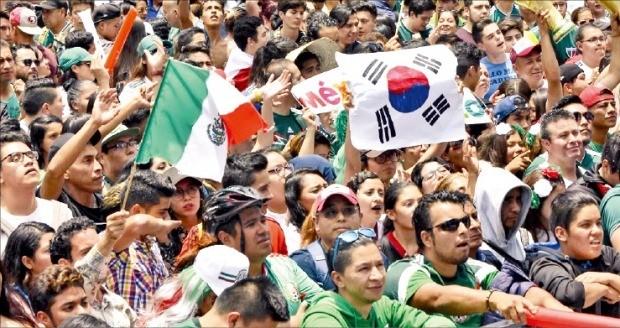 러시아월드컵 조별리그 F조 3차전이 열린 27일(현지시간) 멕시코 시민들이 멕시코시티에서 스크린으로 경기를 지켜보며 태극기와 멕시코 국기를 들고 응원전을 펼치고 있다. /AFP연합뉴스