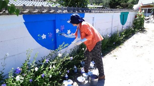 이향재 씨가 마을담장에 벽화를 그리는 모습. 김경래 OK시골 대표 제공