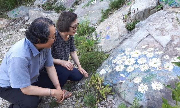 권오택 이향재 부부가 마당의 돌에 그린 그림 앞에 앉아있다. 김경래 OK시골 대표 제공