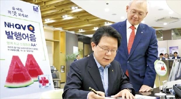 김광수 NH농협금융지주 회장(왼쪽)이 2일 서울 여의도 NH금융PLUS 영업부금융센터에서 정영채 NH투자증권 사장이 지켜보는 가운데 NH투자증권 발행어음 신상품에 가입하고 있다. /NH투자증권 제공