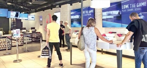 영국 런던 트래펄가광장 인근 아고스 매장에서 소비자들이 태블릿PC와 카탈로그를 보면서 상품을 고르고 있다. /안재광 기자
