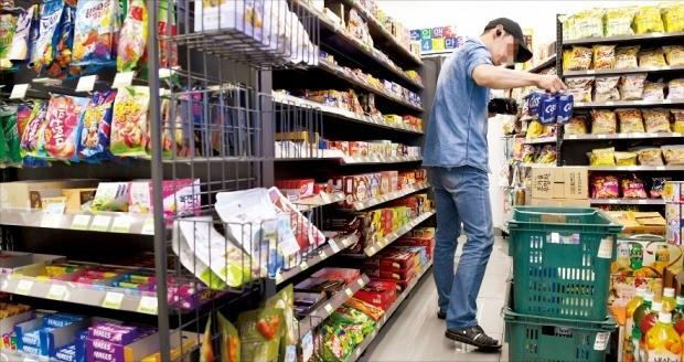 지난 14일 내년 최저임금이 올해보다 10.9% 인상된 시간당 8350원으로 확정된 이후 편의점 본사에 가맹문의 전화가 뚝 끊기고 신규 계약 포기도 잇따르고 있다. 서울 중구의 한 편의점 주인이 상품을 정리하고 있다. /신경훈 기자 khshin@hankyung.com