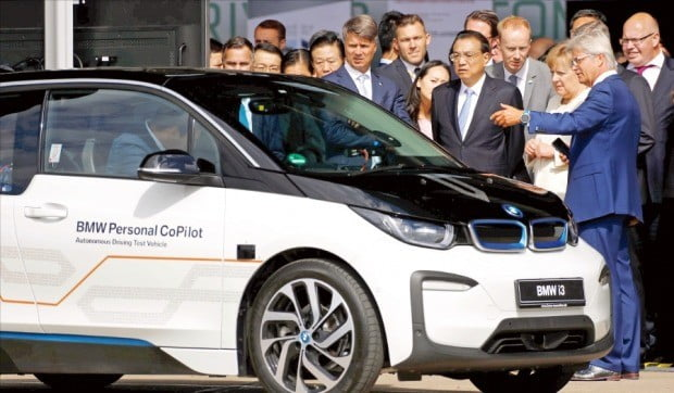 하랄트 크뤼거 BMW 최고경영자(CEO·앞줄 왼쪽 첫 번째)가 지난달 10일 독일 베를린 템펠호프 공항에서 앙겔라 메르켈 독일 총리(세 번째), 리커창 중국 총리(두 번째)와 BMW 전기차 i3에 대해 얘기하고 있다.  /연합뉴스