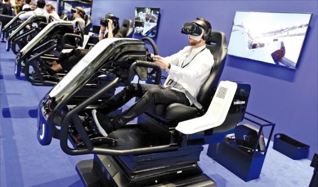 < 삼성, 車 경주 VR 체험 > 삼성전자는 31일 독일 베를린에서 열린 'IFA 2018'에서 미래의 삶을 엿볼 수 있는 첨단 제품을 다양하게 소개했다. 삼성전자 부스를 찾은 관람객이 가상현실(VR) 헤드셋을 쓰고 자동차 경주 체험을 하고 있다.  /연합뉴스