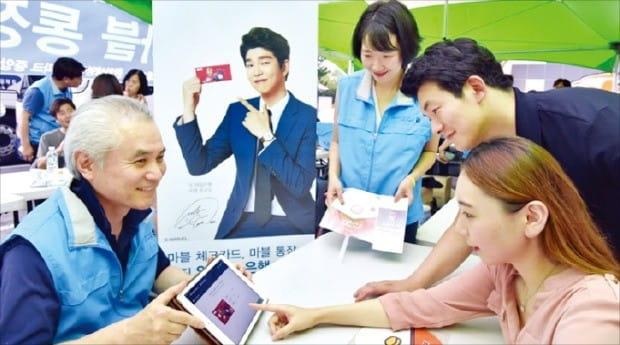 박종복 SC제일은행장(왼쪽 첫 번째)이 태블릿PC를 들고 직접 금융소비자를 찾아 나서는 '찾아가는 뱅킹 서비스'를 안내하고 있다. /SC제일은행 제공