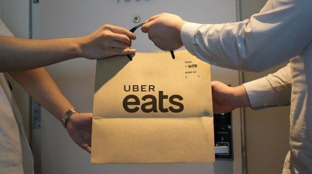 우버이츠 배달 파트너가 소비자에게 음식을 전달하고 있다. 한경DB