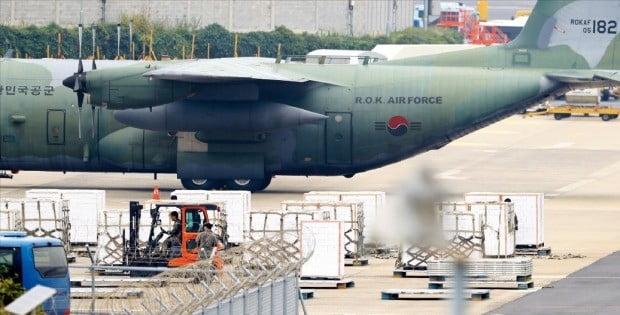 < 제주산 귤 싣고 北으로 > 평양행 제주산 감귤 50t을 수송할 공군 C-130 수송기가 11일 제주국제공항에 계류 중이다. 군 장병들이 수송기에 실을 귤 상자를 최종 점검하고 있다.  /연합뉴스