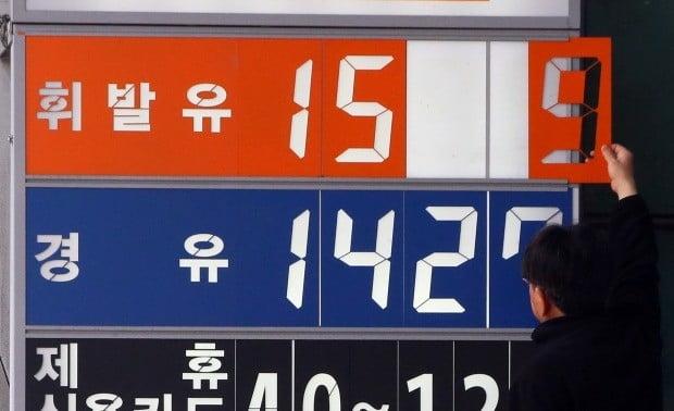 정부가 유류세 인하에 돌입한 지난 6일 서울 영등포구의 한 주유소에서 주유소 관계자가 휘발유 가격을 '1591원'으로 조정하고 있다.  사진=연합뉴스