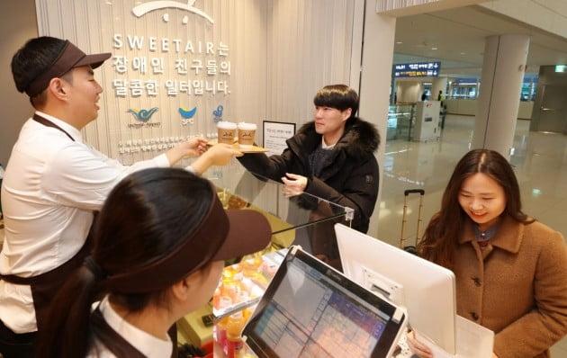 인천공항 제2여객터미널 1층 입국장 중앙에 오픈한 장애인 고용매장 '스윗에어카페'에서 여객들이 음료를 주문하고 있다. 인천공항공사 제공