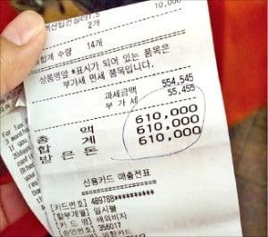 한 외국인이 14개 화장품을 61만원에 결제한 영수증을 들어 보이고 있다. 이 외국인은 종업원이 주문하지도 않은 품목까지 포함해 결제했다고 주장했다. /구민기 기자 kook@hankyung.com