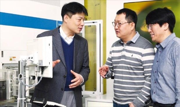 정원철 삼성전자 반도체연구소 수석연구원(왼쪽)이 팀원들과 반도체 설비를 보며 토론하고 있다.  /삼성전자  제공