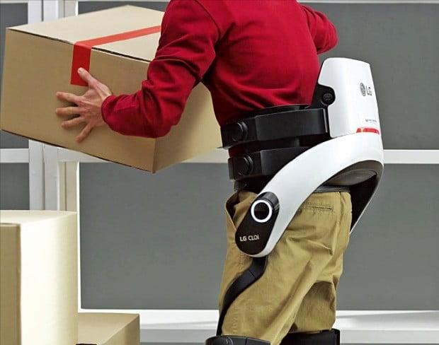 한 근로자가 허리 근력을 보조하는 'LG 클로이 수트봇'을 입고 무거운 짐을 나르고 있다. /LG전자 제공
