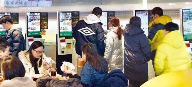 < 확산되는 무인주문기 > 서울 동자동의 맥도날드 서울역점에서 4일 소비자들이 무인주문기 화면을 보며 메뉴를 고르고 있다.  /허문찬  기자  sweat@hankyung.com