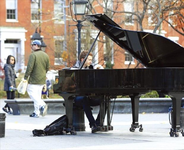 그리니치 빌리지 워싱턴 스퀘어 파크에서 피아노를 연주하는 한 남성.