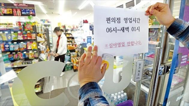 최저임금 인상으로 인건비 부담이 커지자 심야시간에 영업을 포기하는 편의점이 늘고 있다. 서울 중구의 한 편의점 점주가 새벽 1~6시 문을 열지 않는다는 내용의 안내문을 붙이고 있다.  /허문찬 기자 sweat@hankyung.com
