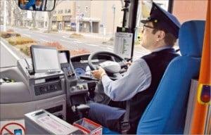 """자율주행 버스 운전사 가노 야스유키 씨는 """"두 손을 핸들 위에 올려놓고 비상시에만 조작한다""""고 말했다."""