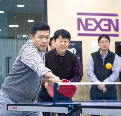 강호찬 넥센타이어 사장(왼쪽)이 넥센강남타워 1층에 있는 문화공간에서 직원들과 탁구를 즐기고 있다.  /넥센타이어 제공