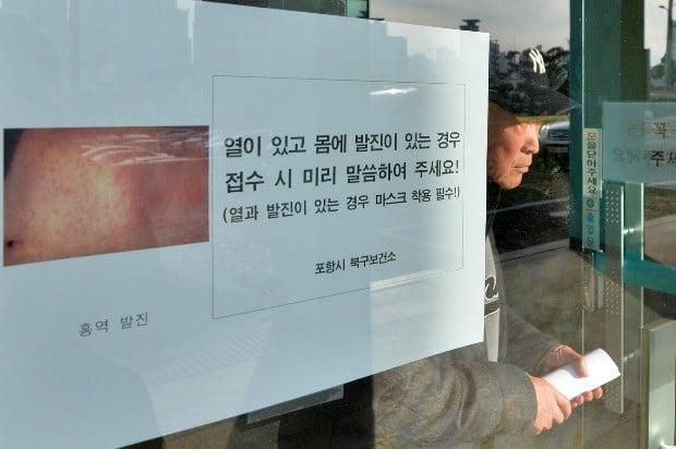 보건소 출입문에 홍역 의심증세가 있으면 미리 알려달라는 홍보문이 부착돼 있다. / 사진=연합뉴스