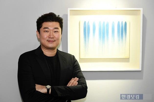 2억1000만원에 공동구매한 이우환의 '선으로부터' 옆에 선 김재욱 대표