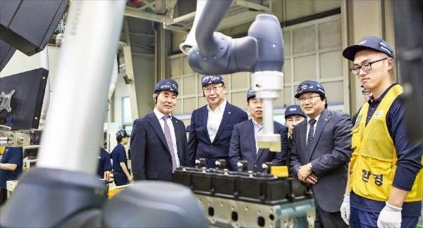 두산인프라코어와 한국로봇산업진흥원 관계자들이 협동로봇 설치 안전인증 1호를 획득한 인천공장 G2엔진 생산공정을 살펴보고 있다.  /두산인프라코어  제공