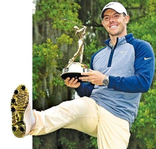 황금트로피에 황금골프화 '환상의 궁합' 로리 매킬로이가 17일(현지시간) PGA투어 플레이어스 챔피언십을 제패한 뒤 이번 대회부터 주기 시작한 금장 우승 트로피를 든 채 한정판으로 제작된 '황금 골프화'를 내보이고 있다. 매킬로이는 후원사인 나이키와 공동으로 황금골프화를 디자인했다. /USA투데이연합뉴스