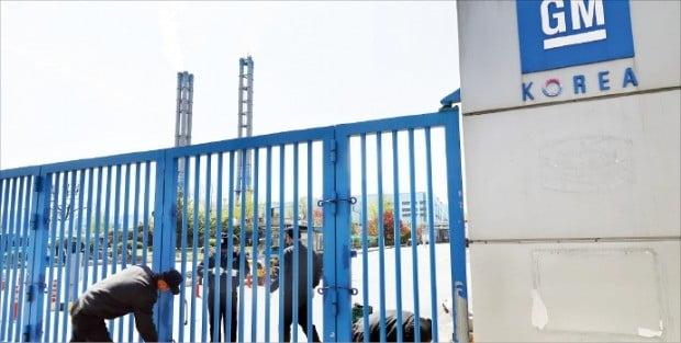 한국GM 노동조합은 지난해 4월 18일 인천 부평공장에서 경영진의 군산공장 폐쇄 결정 등에 항의하는 결의대회를 열었다. 노조원들이 결의대회에 앞서 정문을 걸어 잠그고 있다.  /연합뉴스