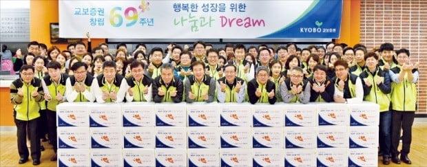 김해준 교보증권 사장(앞줄 왼쪽 일곱 번째)을 비롯한 임직원들이 작년 11월 '김장김치 담그기' 행사에 참석해  '손가락 하트'를 만들어 보이고 있다.