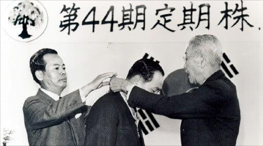 1969년 44기 주주총회에서 유일한 창업자(오른쪽)가 전문경영인 조권순 사장에게 경영권을 이양하고 있다.