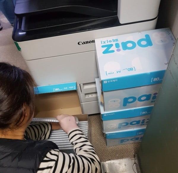 복사실 직원이 단속을 피해 숨겨놓은 불법 제본된 서적들을 정리하고 있다.