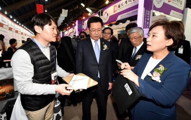 박남춘 인천광역시장(가운데)이 17일 8부두 상상플랫폼에서 열린 '2019 도시재생 산업박람회'에서 김현미 국토교통부 장관(오른쪽)과 박람회 부스를 둘러보고 있다. 인천시 제공