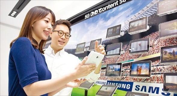 삼성전자 직원들이 지난 13일 경기 수원 삼성 디지털시티에서 5세대(5G) 이동통신 속도를 활용해 태블릿으로 초고화질 동영상 스트리밍을 시연하고 있다. /삼성전자 제공