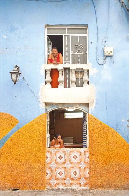 창밖을 내다보며 여유로운 일상을 즐기는 쿠바 사람들.