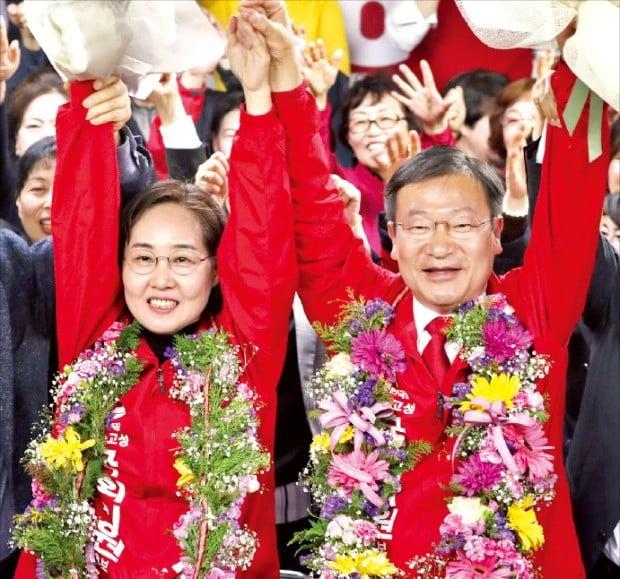 정점식 자유한국당 당선자(오른쪽)가 4·3 보궐선거 통영고성 선거구에서 승리한 뒤 선거 사무실에서 지지자들과 손을 맞잡아 올리며 환호하고 있다. 왼쪽은 부인 최영화 씨.  /연합뉴스