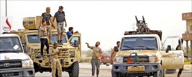 이동 중인 리비아 통합정부(GNA)군 소속 군인들이 트리폴리 남부 70㎞ 지점에서 쉬고 있다. GNA군은 이달 초부터 리비아 동부 군벌 하프타르가 이끄는 리비아국민군(LNA)과 트리폴리 외곽 지역에서 교전을 벌이고 있다. 유엔은 이번 내전으로 최소한 264명이 사망했다고 발표했다.  /AFP연합뉴스