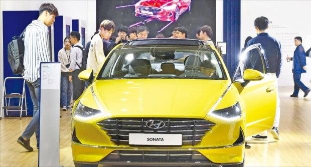 '월드IT쇼 2019' 관람객이 현대자동차 전시관에서 스마트폰으로 문을 여닫을 수 있는 신형 쏘나타를 살펴보고 있다.  /김범준 기자 bjk07@hankyung.com