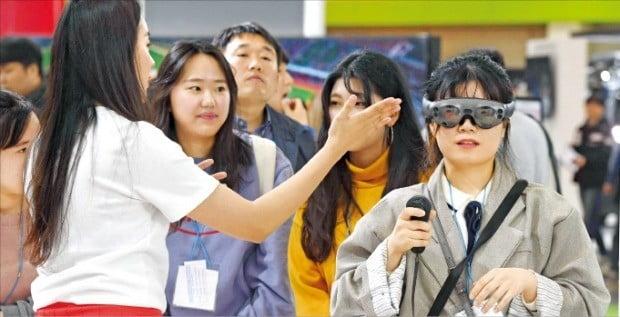 '월드IT쇼 2019' 사흘째인 26일 한 관람객이 SK텔레콤 전시관에서 증강현실(AR) 게임을 즐기고 있다.  /신경훈 기자 khshin@hankyung.com