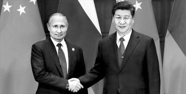 < 시진핑·푸틴, 의기투합 > 시진핑(習近平) 중국 국가주석(오른쪽)이 26일 베이징에서 열린 '일대일로 국제협력 정상포럼'에서 중국 주도의 일대일로 정책을 강하게 추진하겠다는 뜻을 밝혔다. 시 주석과 포럼에 참석한 블라디미르 푸틴 러시아 대통령이 악수하고 있다.  /타스연합뉴스